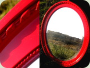 Oval red lacquered                           wall mirror labeled Ota