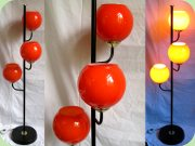 Black lacquered floor                           lamp with 3 orange glass shades